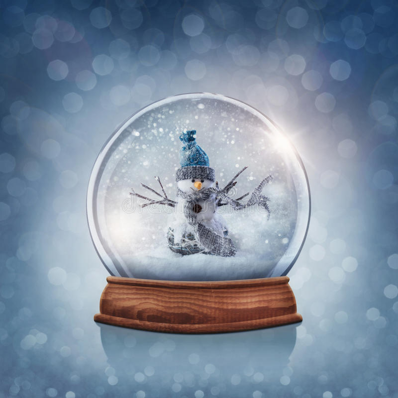 Snow globe with snowman. On a blue background stock photography