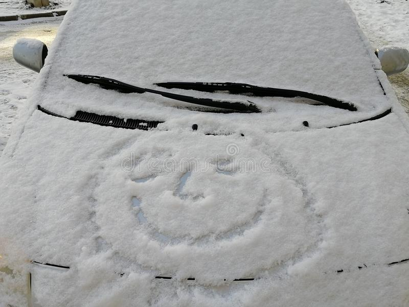 Snow happy face on the car window. Smile in the snow, happy cheerful image. royalty free stock photography
