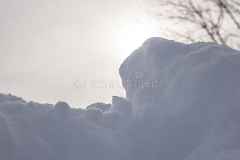 Snow with Hazy Sun Behind It. Snow in front of nice hazy sunshine which is partially blocked by its edge stock photos