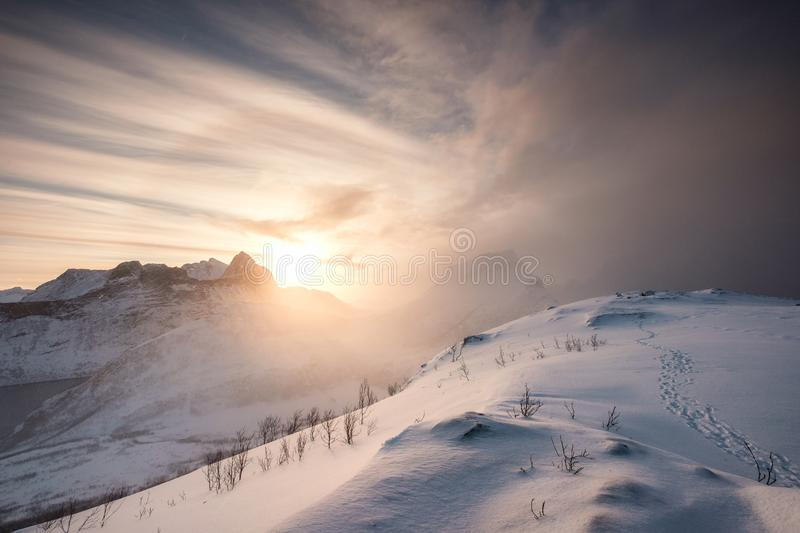 Snow hill with sunrise on mountain range stock photography