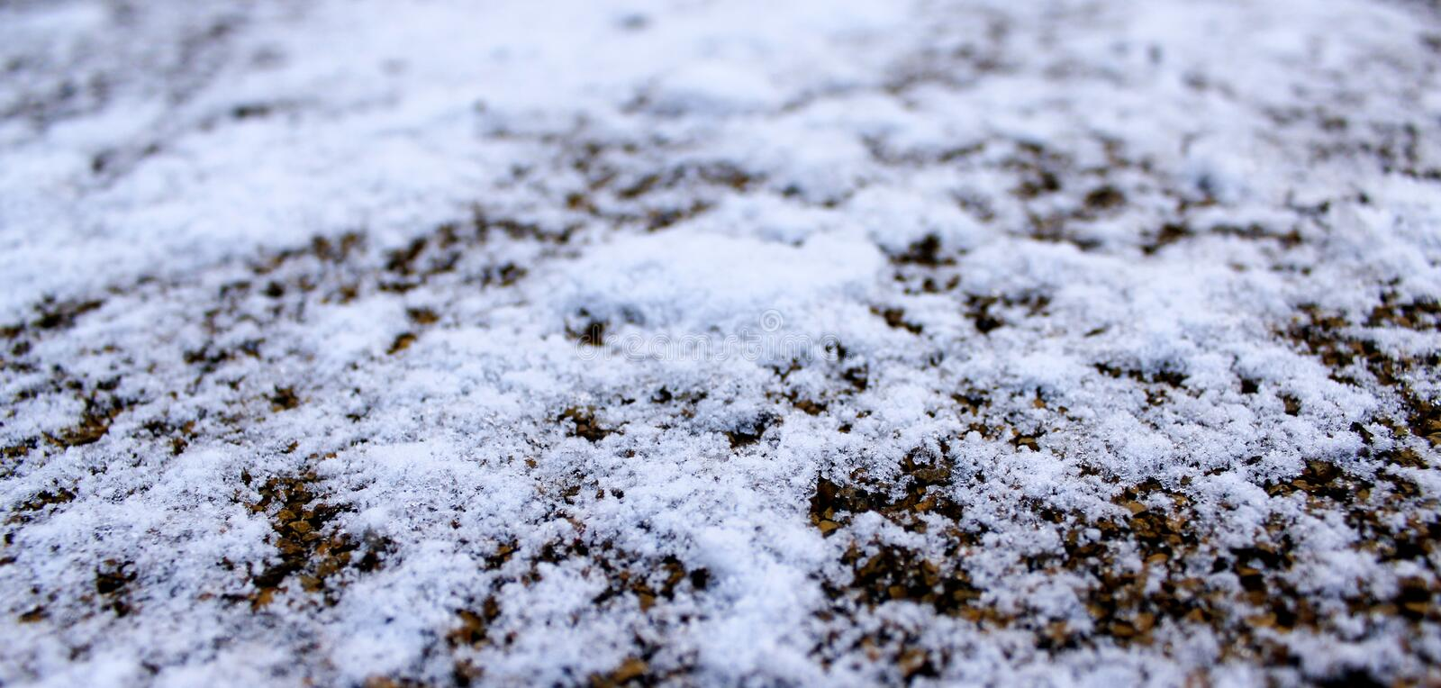 Snow and ice on brown small stones and sand background stock image