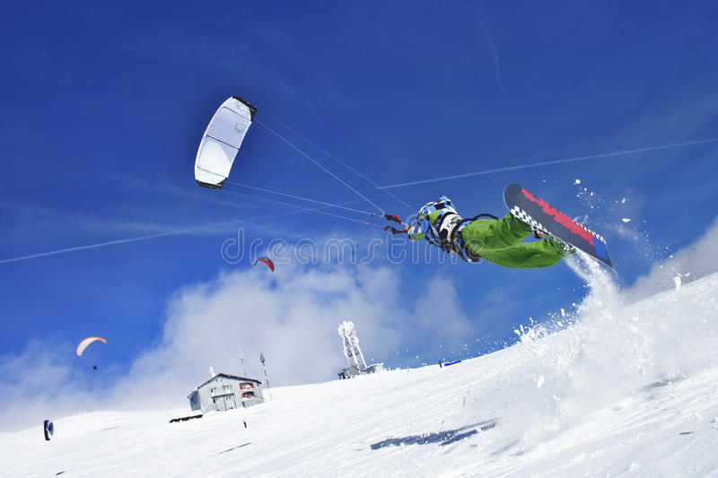 Snow kiter. Snow kite jumper, a blue sky and in the background, other paraglides and kites stock photos