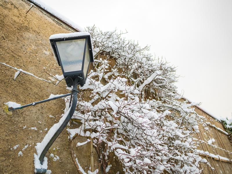 Snow on lamp in the wall winter with copy space stock photography