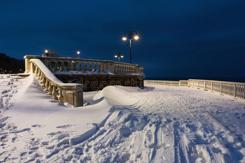 Snow landscape in Burgas Sea Garden, near the Culture center Sea Casino at blue hour. Winter sunset over the sea in Burgas bay, Black Sea, Bulgaria royalty free stock images