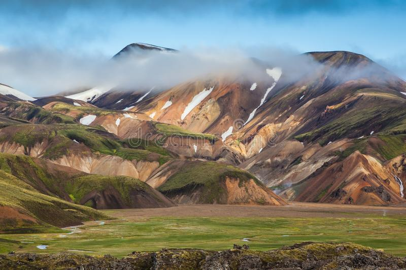 Snow lies in the hollows of multicolored mountains royalty free stock photo