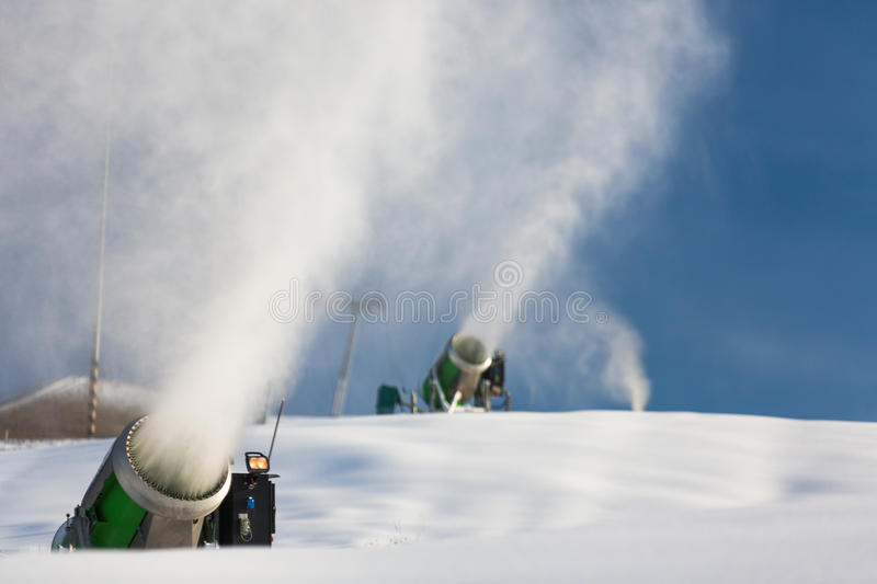 Snow-machine bursting artificial snow over a skiing slope stock photo