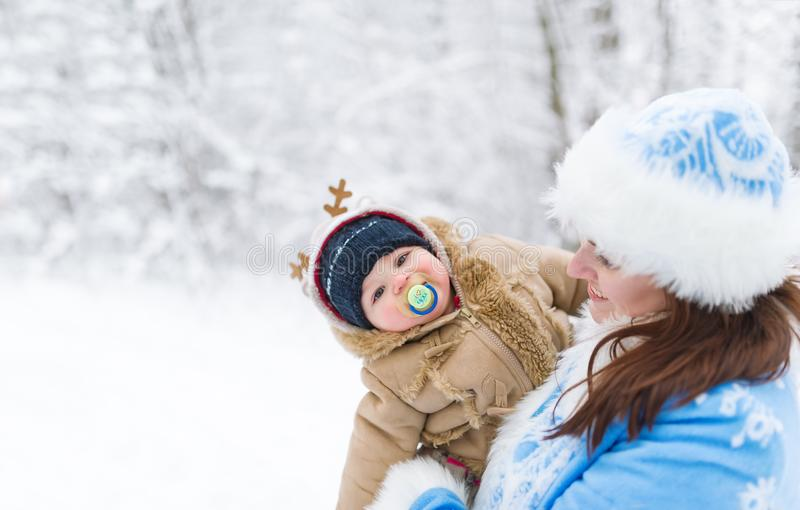 Snow maiden and baby boy embracing in a winter park amoung trees branches. royalty free stock photo
