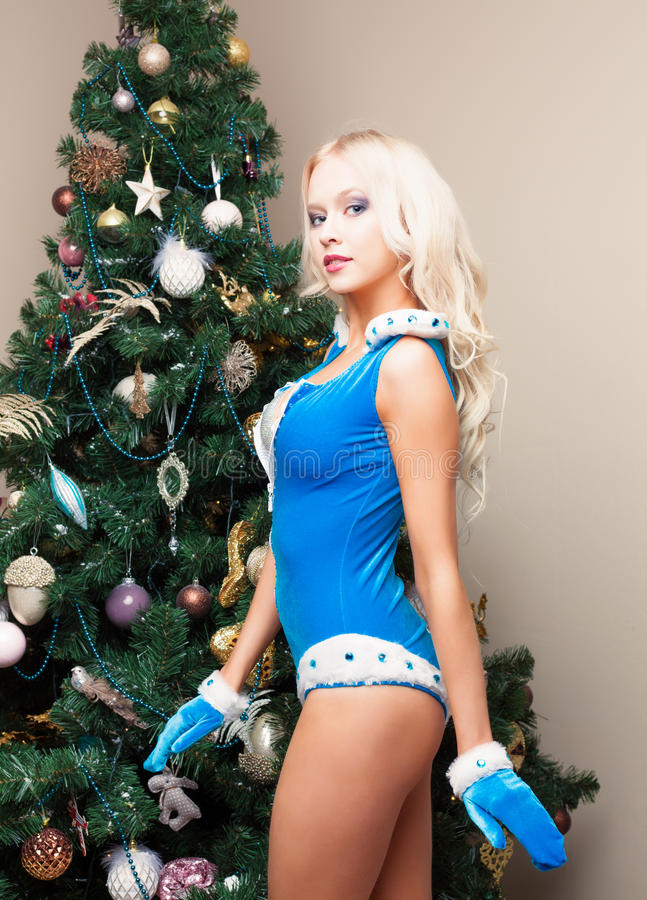 Snow Maiden young woman in a blue suit and gloves at the Christmas tree. Standing in profile. New year, christmas, x-mas, new stock images