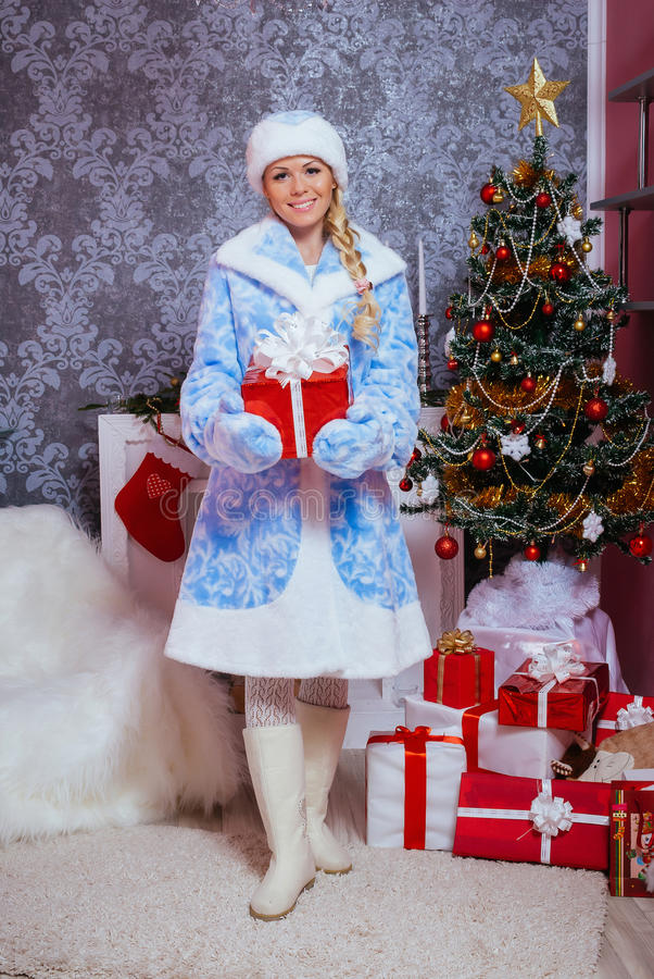 Snow Maiden (Snegurochka) holding a New Year gift royalty free stock photography