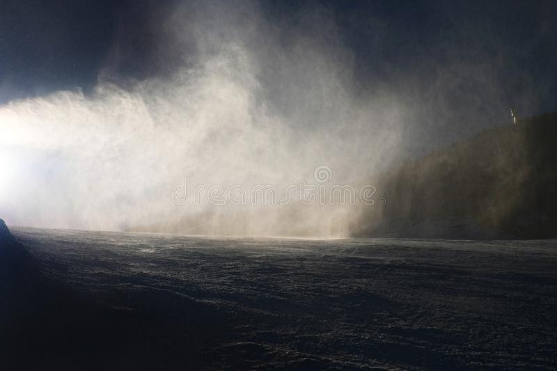 Snow making on slope. Skier near a snow cannon making fresh powder snow. Mountain ski resort in winter calm. royalty free stock photography