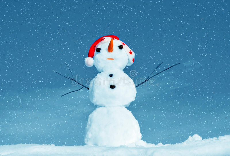 Snow man in santa cap on nature royalty free stock photography