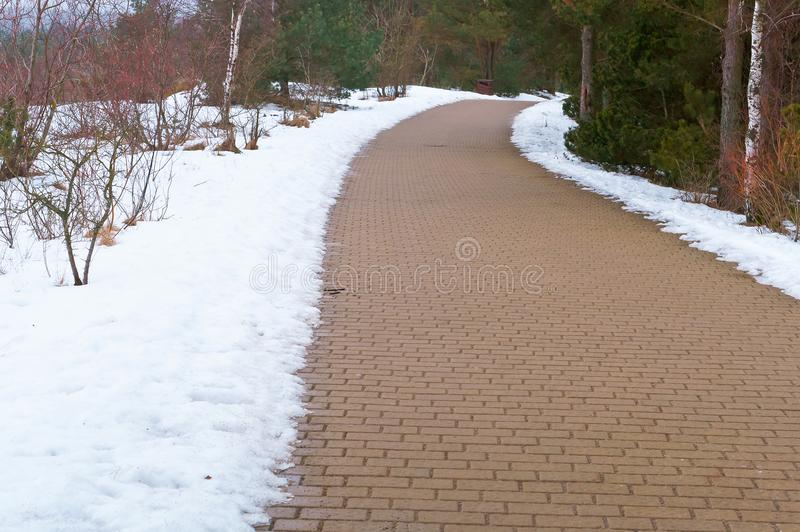 The path of paving slabs cleared of snow, snow melted on the dirty side of the road. Snow melted on the dirty side of the road, the path of paving slabs cleared royalty free stock photos