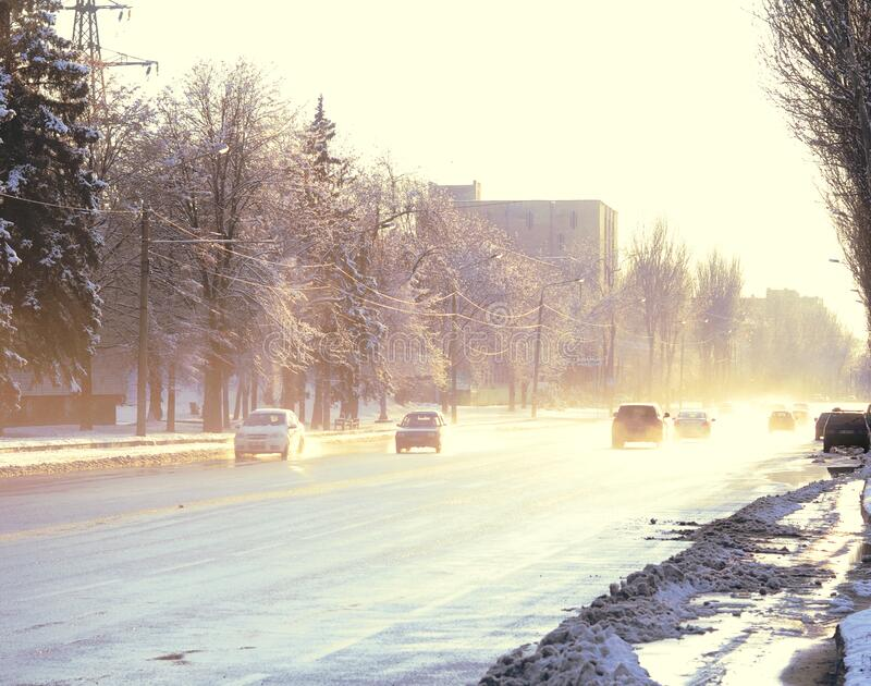Snow melting in the city road with cars. Sunset time background stock photos