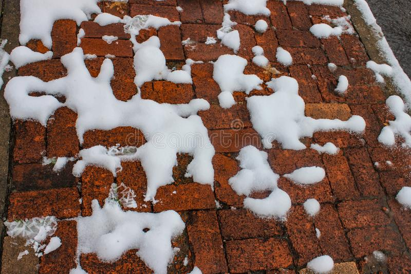 Snow melting but still visiable in blobs on orangish broken brick sidewalk stock images
