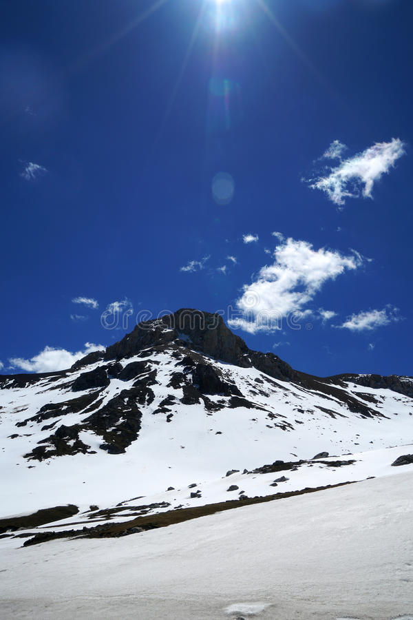 Snow mountain Blue Sky. Snow mountain is under the dark blue sky and white clouds stock photography