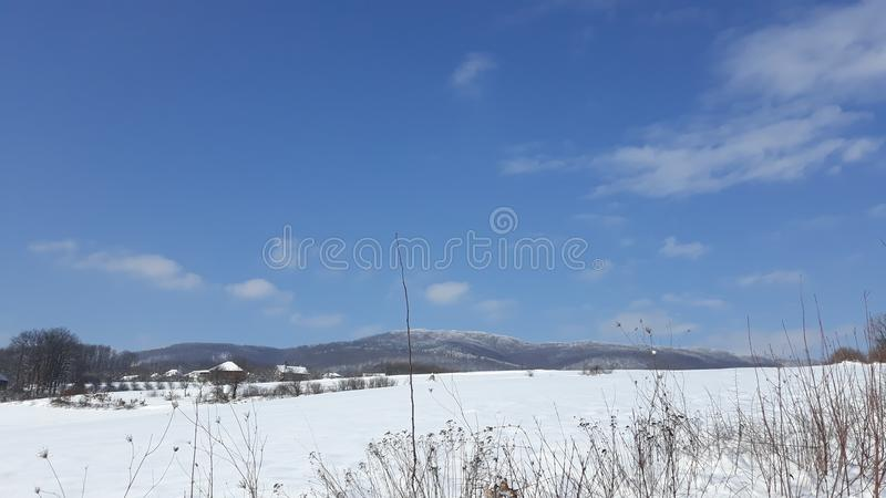 Snow mountain on blue sunny sky royalty free stock photography