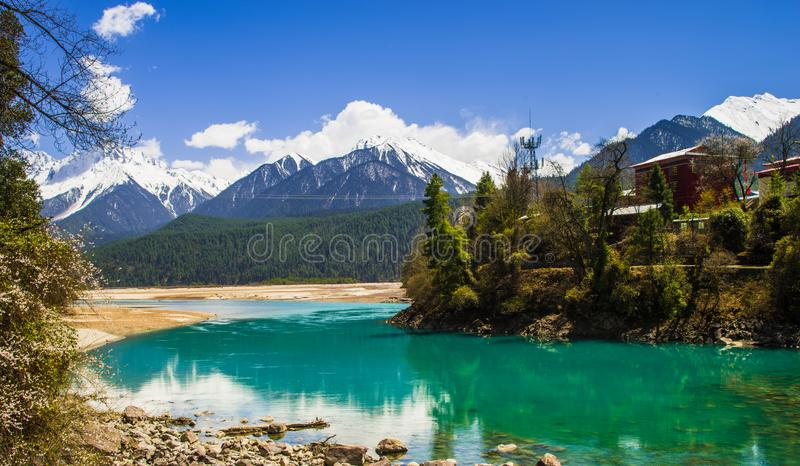 Snow mountain , clear green river landscape of valley. Green water , snow mountain , white clouds , landscape of river valley in Tibet , China stock photo