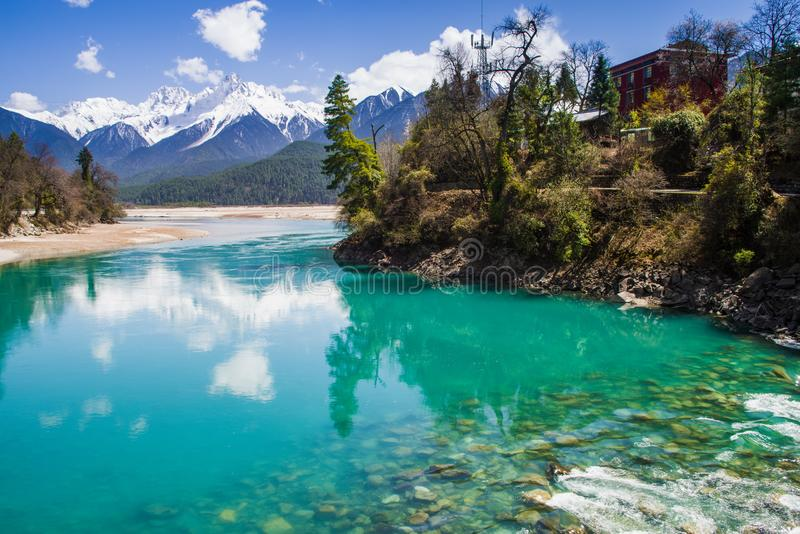 Snow mountain , clear green river landscape of valley. Green water , snow mountain , white clouds , landscape of river valley in Tibet , China royalty free stock images