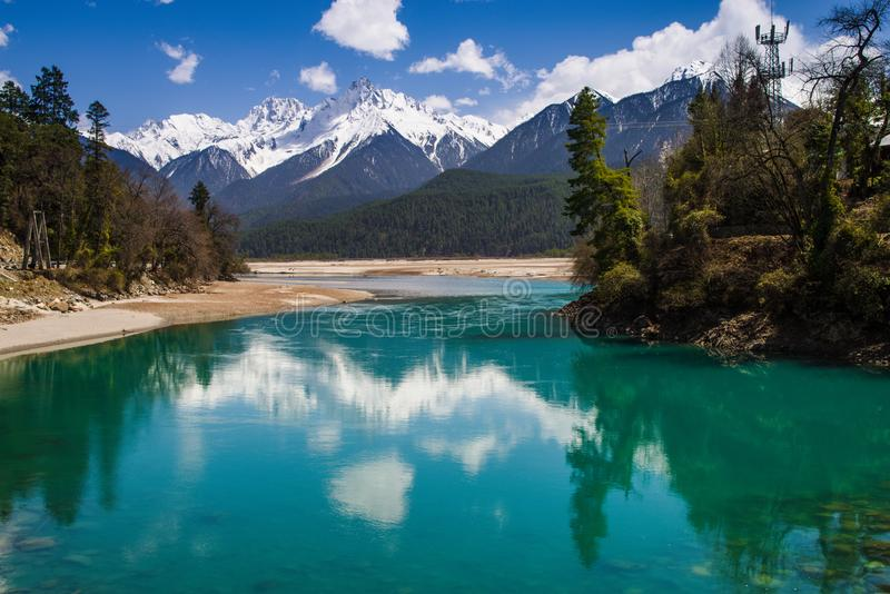 Snow mountain , clear green river landscape of valley. Green water , snow mountain , white clouds , landscape of river valley in Tibet , China royalty free stock image