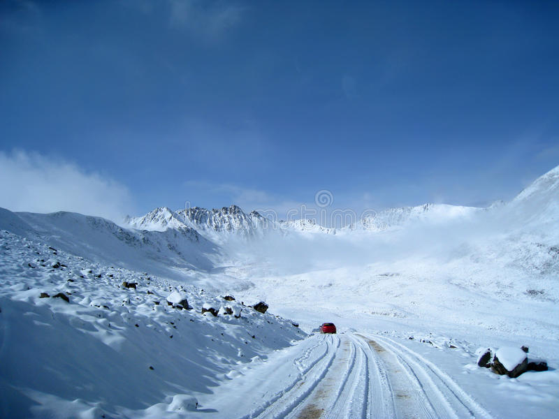 Snow mountain with red car stock images
