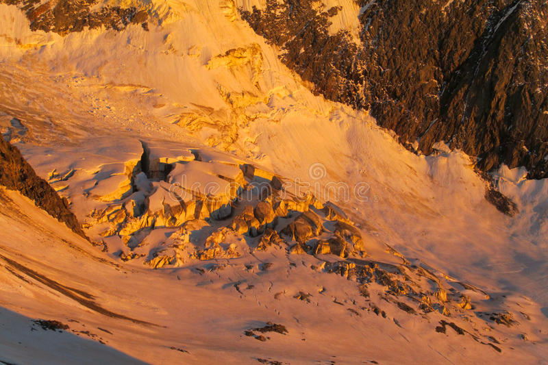 Snow mountain ridge in Alps at sunset. Snow mountain ridge in Alps, white snow summit at sunset orange light royalty free stock photo