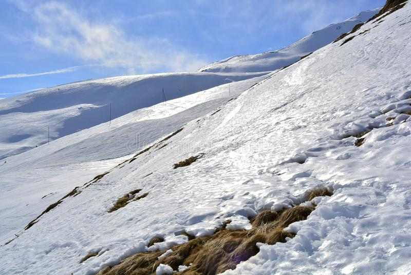 Snow mountain with sunshine and a grass pitch royalty free stock photography