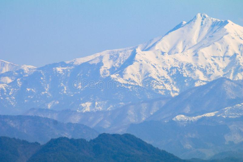 The snow on the mountain on blue sky background. The snow on the mountains on blue sky background stock images