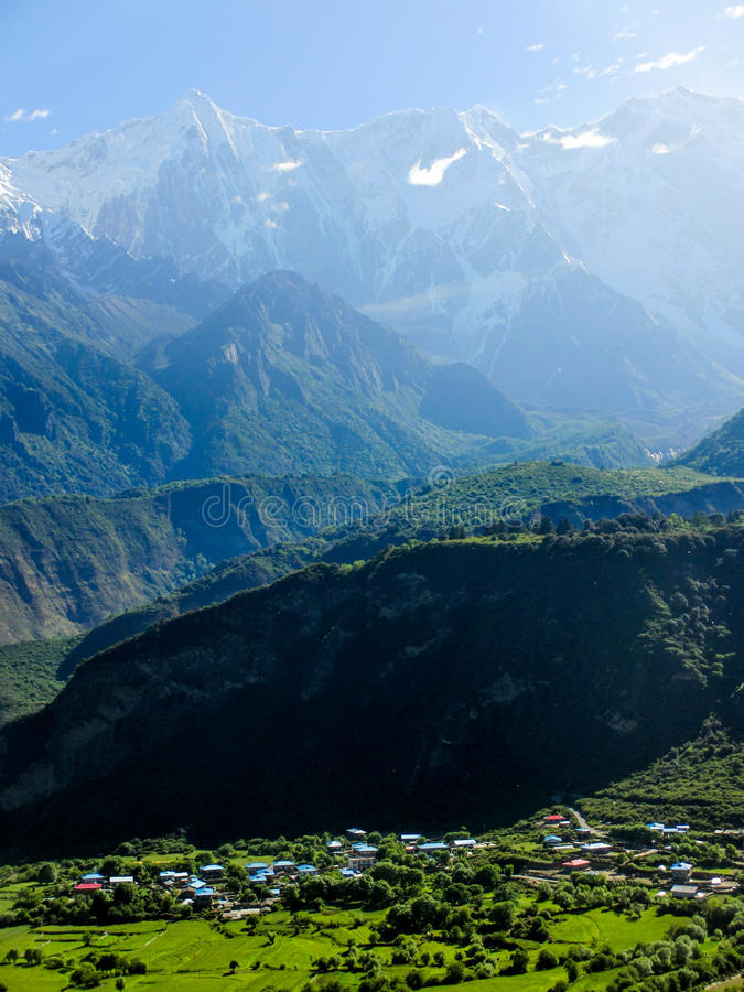 Snow mountains and village at Brahmaputra River stock image