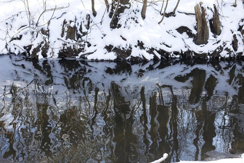 Snow in the park bright sunny happy winter day. Trees are reflected in the water surface. royalty free stock photos