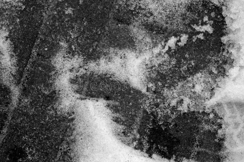 Snow on pavement in black and white stock image