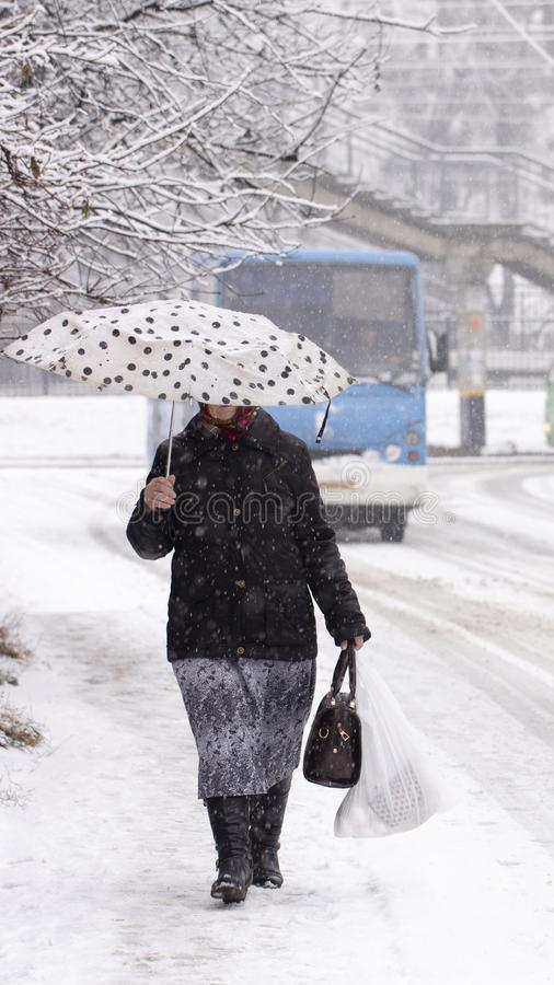 Snow on people on umbrellas who walk down the street during a snowfall Cityscape stock photography