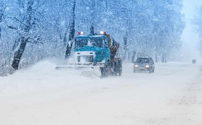 Snow plow doing snow. Removal during blizzard stock photo