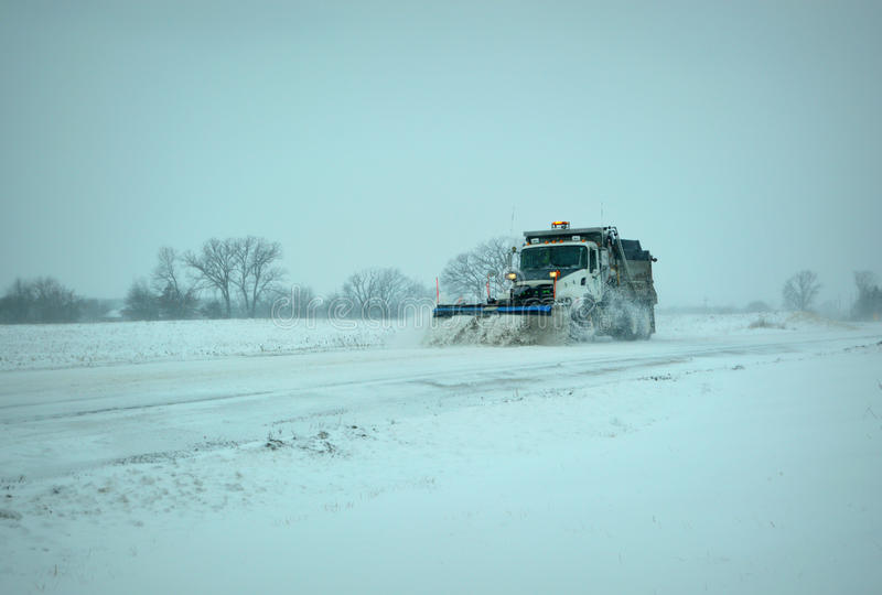 Snow Plow. A township snow plow, with a blue plow, plowing the streets during a winter snow storm royalty free stock photos