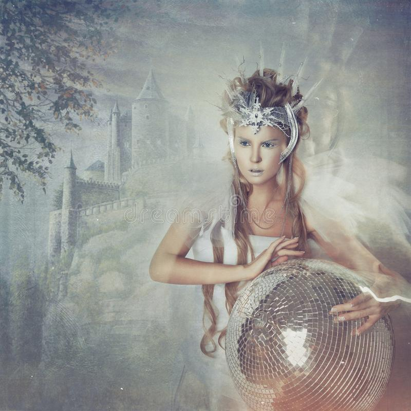 The snow Queen on the background of the castle. The snow Queen in the crown on the background of the castle. Blonde girl holding a magic ball royalty free stock image