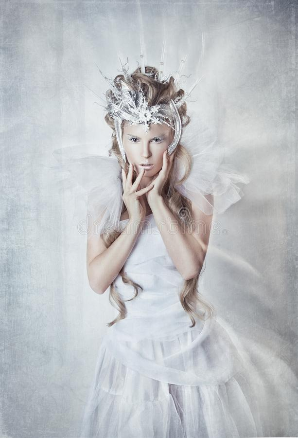The snow Queen in a white dress. Fabulous girl with long hair and silver crown stock photos
