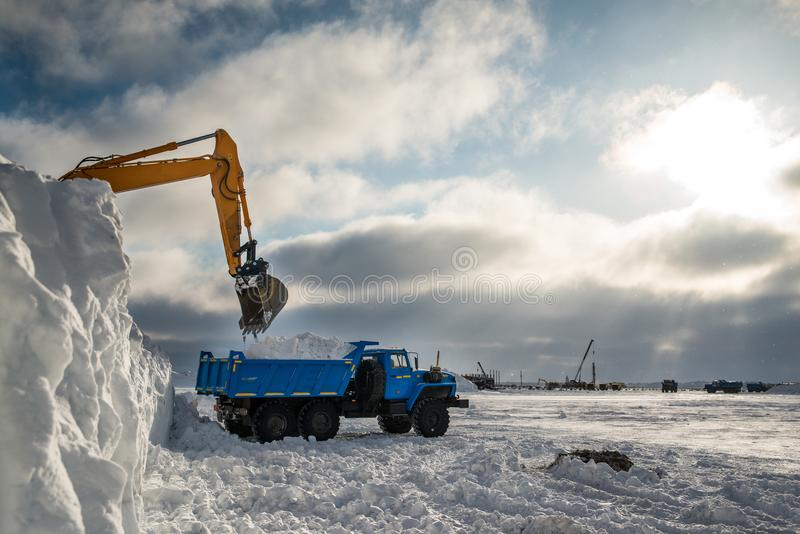 Snow removal in the Arctic. Clearing snow in the Arctic, dump trucks take it out stock photo