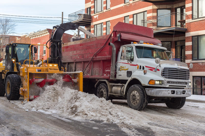 Snow removal in Montreal. Montreal, CA, 5th March 2016. A snow thrower is blowing snow into a dump truck after snow storm royalty free stock images