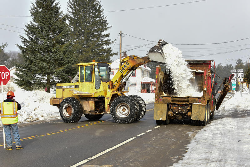 Snow removal. Rusty front end loader and dump truck removing snow from village streets royalty free stock image
