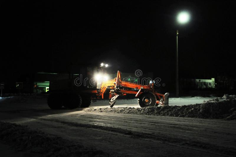 Snow removal tractor cleaning snow, truck silhouette working at night cleaning road, city infrastructure in winter royalty free stock images