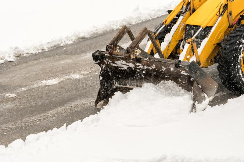 Snow removal. Wheel loader machine or vehicle removing snow from the roads. In winter royalty free stock image