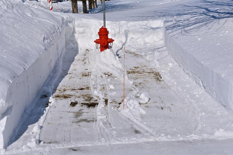 Snow removed from a round a fire hydrant. A snowblower has cleared a path to a fire hydrant allowing firefighters accessibility in case of an emergency stock images