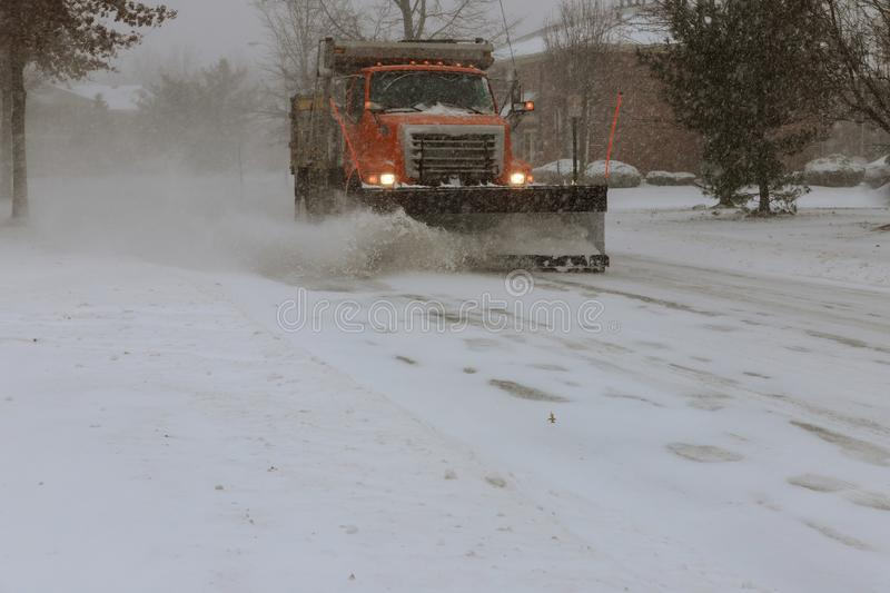Snow-removing machine cleans the street of the city from the snow in the morning snow-covered trees. stock photo
