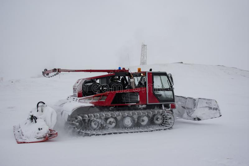 Snow removing machine on mountain slope. In foggy conditions royalty free stock photography