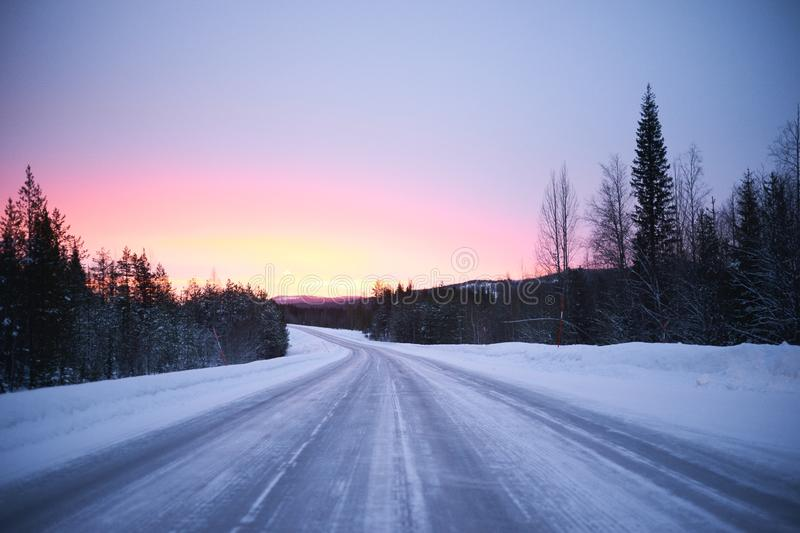 Snow on road through forest, sunrise royalty free stock image