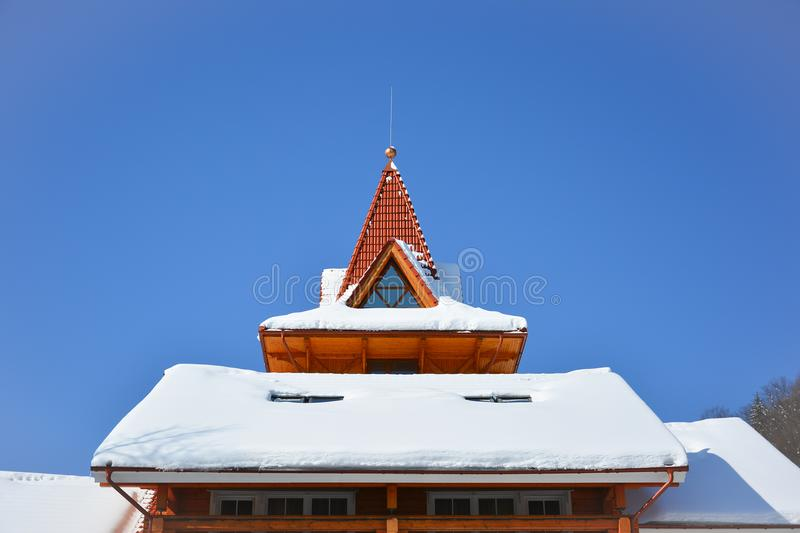 Snow on the roof of wooden house. Attic window of triangular shape on snow-covered roof on background of bright blue sky. Sunny w stock photography