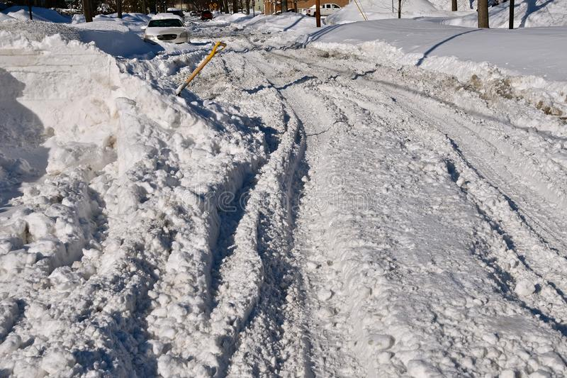 Snow ruts on a street after a snowstorm. An unplowed street in a city with ruts finds ruts and tracks made by vehicles driving after a heavy snowfall stock photography