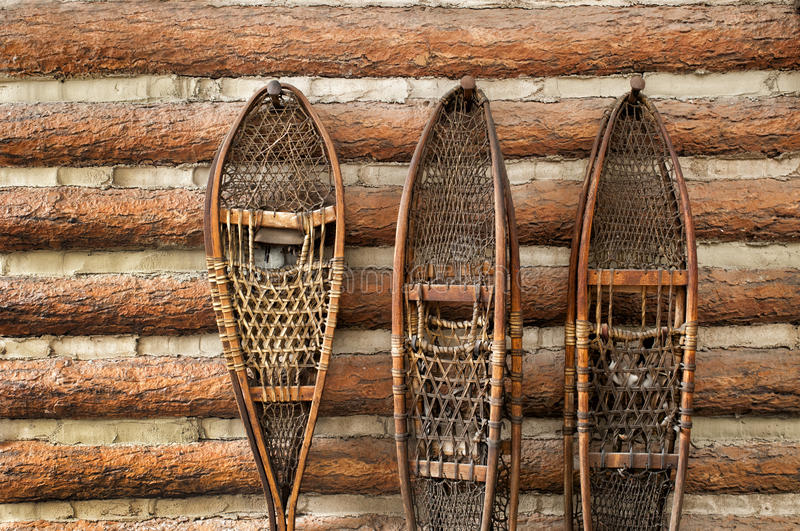 Snow shoes and a log cabin royalty free stock photos