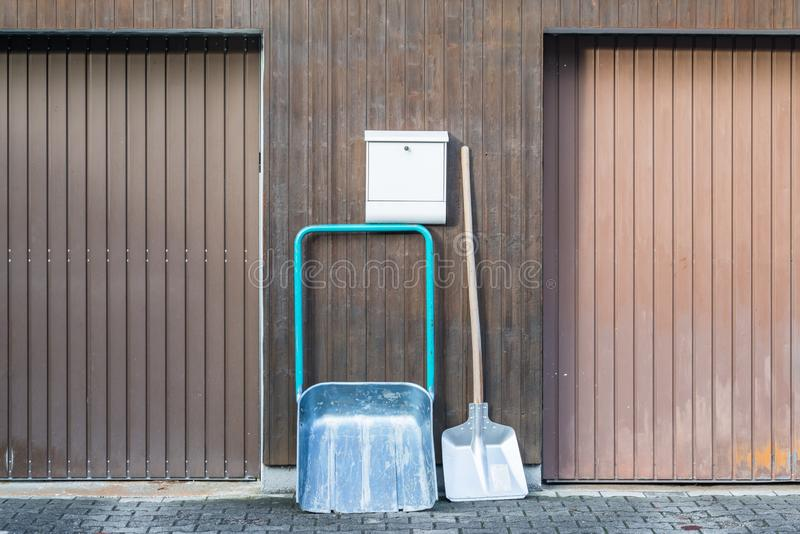 Snow shovel in front of a double garage without snow, Germany.  royalty free stock photos