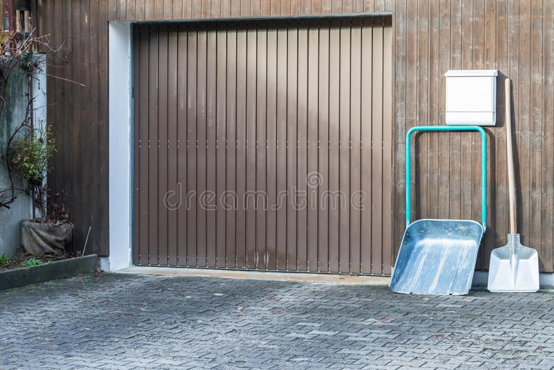 Snow shovel in front of a double garage without snow, Germany.  stock photo