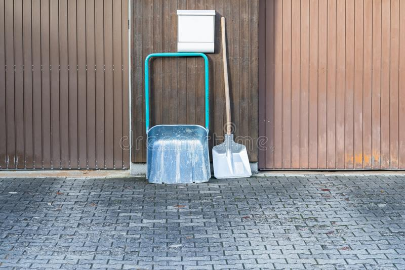 Snow shovel in front of a double garage without snow, Germany.  stock photos